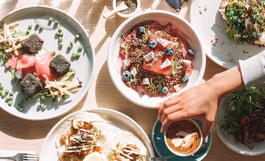 top down view of a sunny brunch meal with hand reaching for coffee
