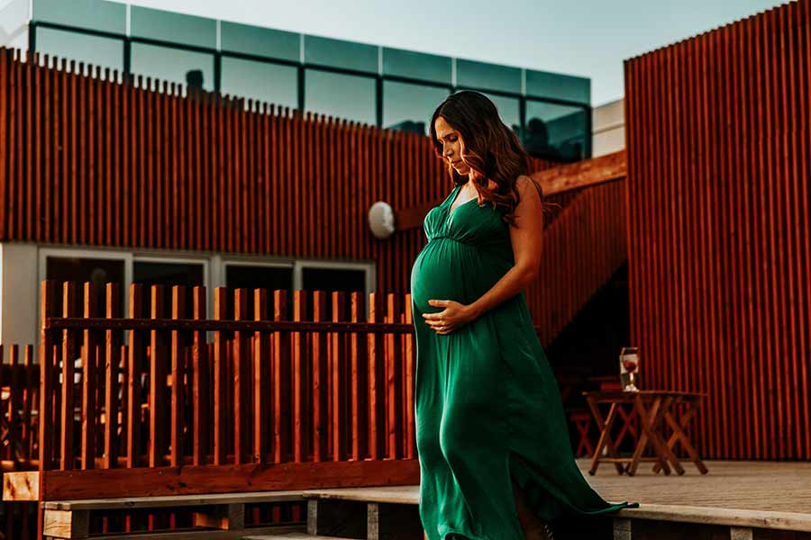 pregnant woman cradling belly in green dress whiile walking outside